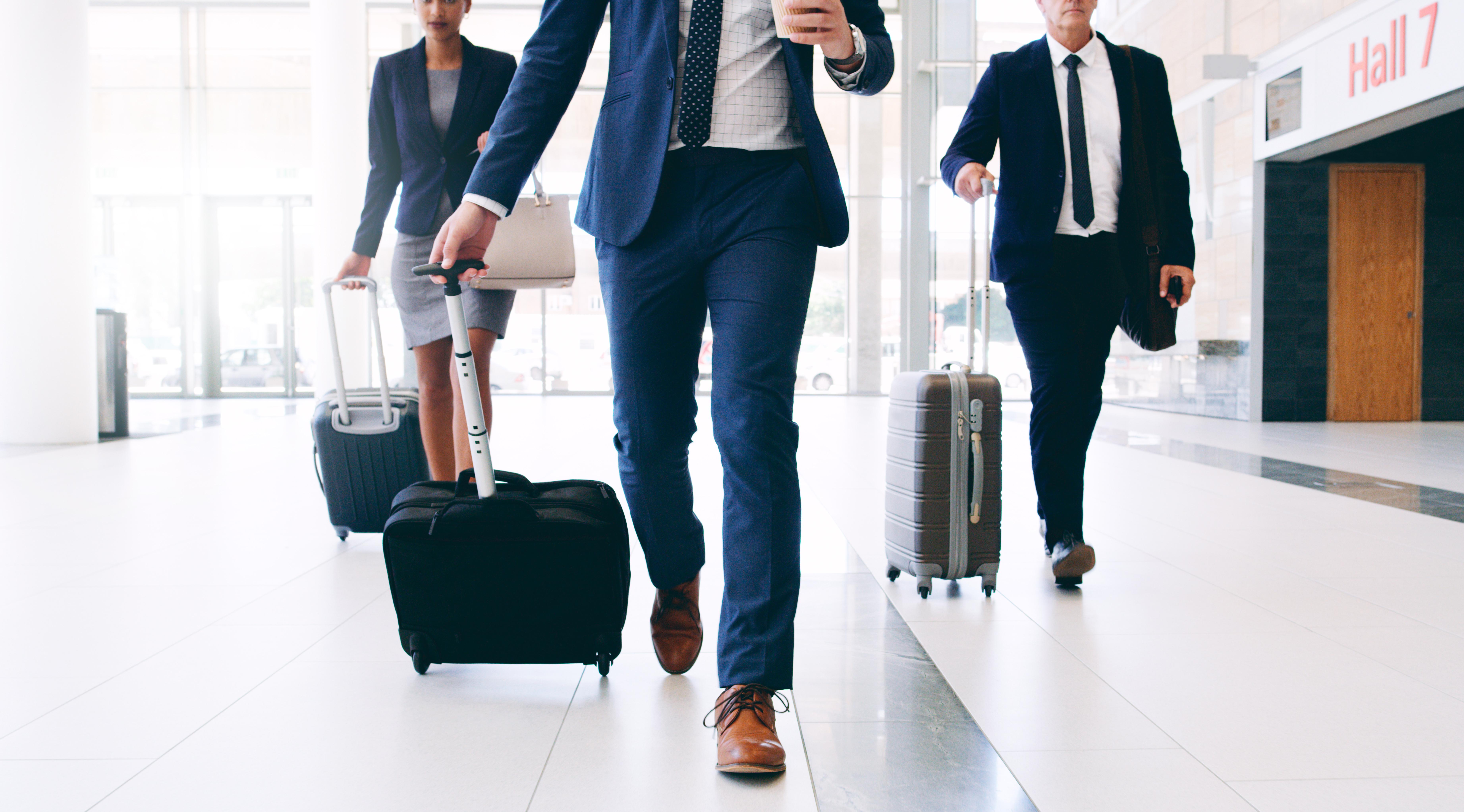 Pasajeros corporativos caminando con maletas por aeropuerto