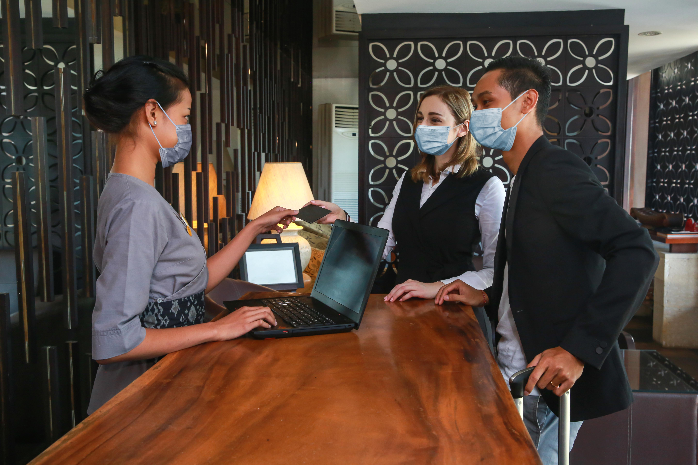 Pasajeros con mascarillas en lobby de hotel
