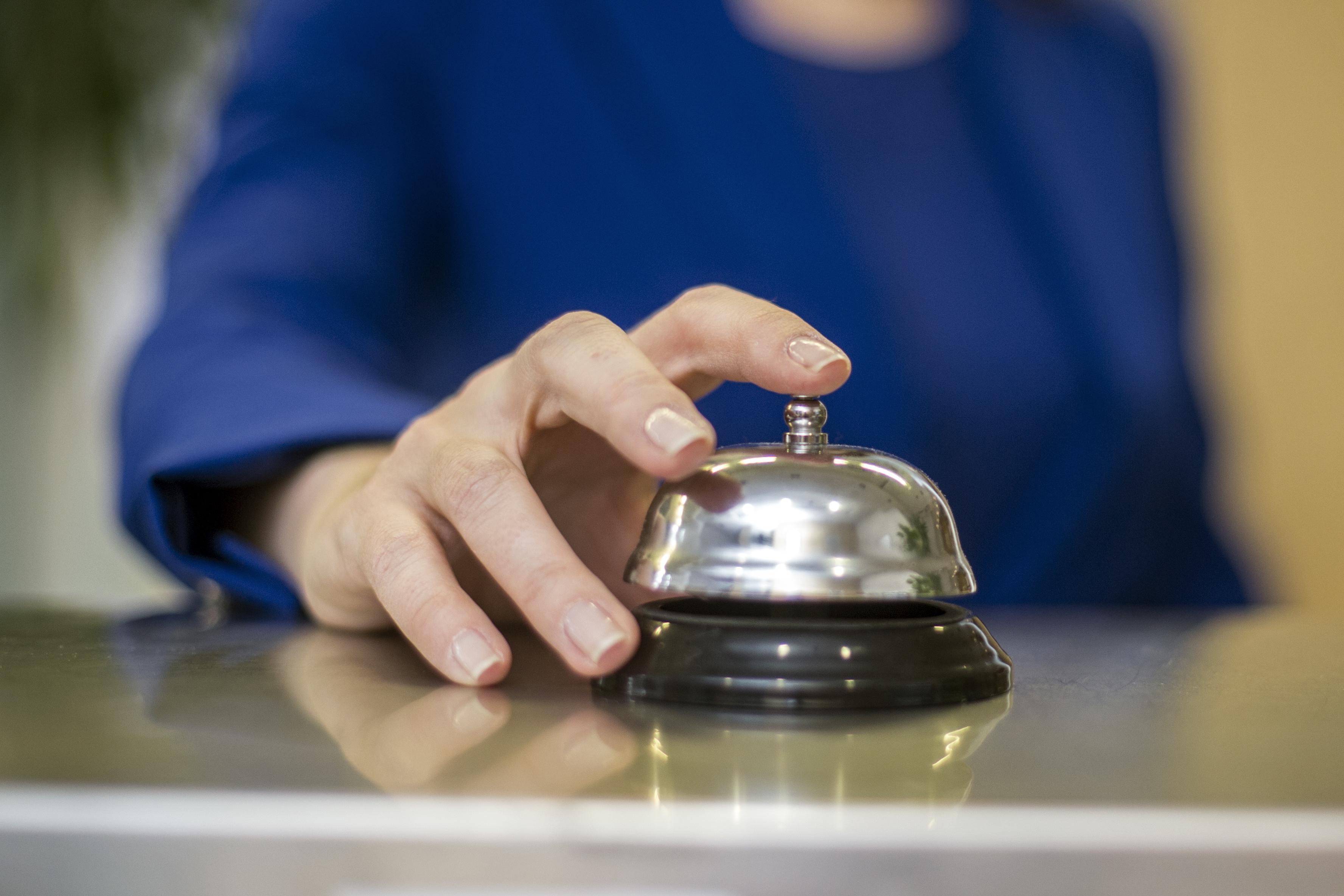 Mano de mujer tocando el timbre de recepción de un hotel