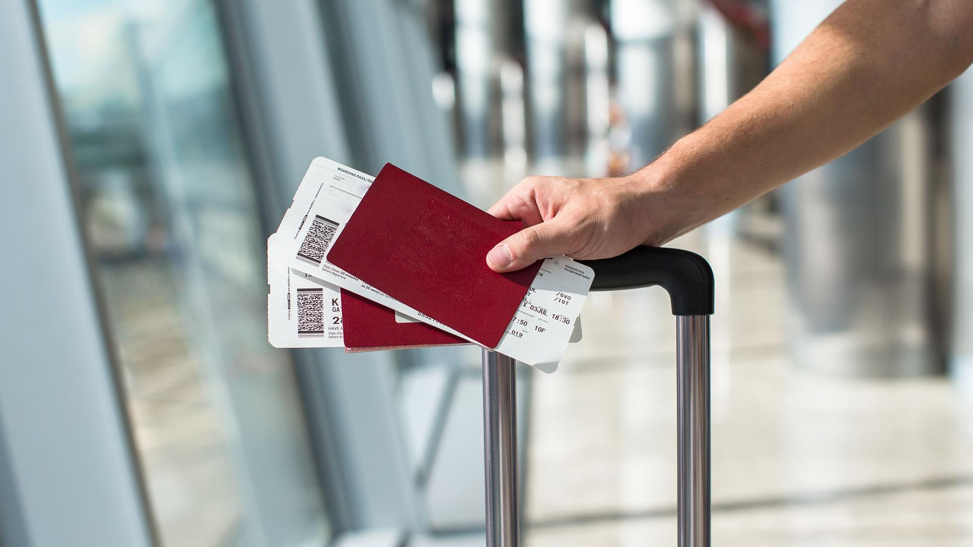 Pasajero con pasajes y pasaporte en mano en aeropuerto